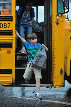 A child steps off a school bus on the first day of school